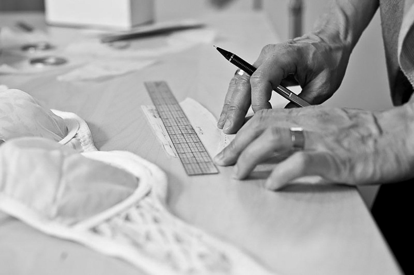 Close up of a woman's hands with a ruler and pencil, making adjustments to a sewing pattern piece for a bra. An unfinished, lacy bra lays on the table nearby.