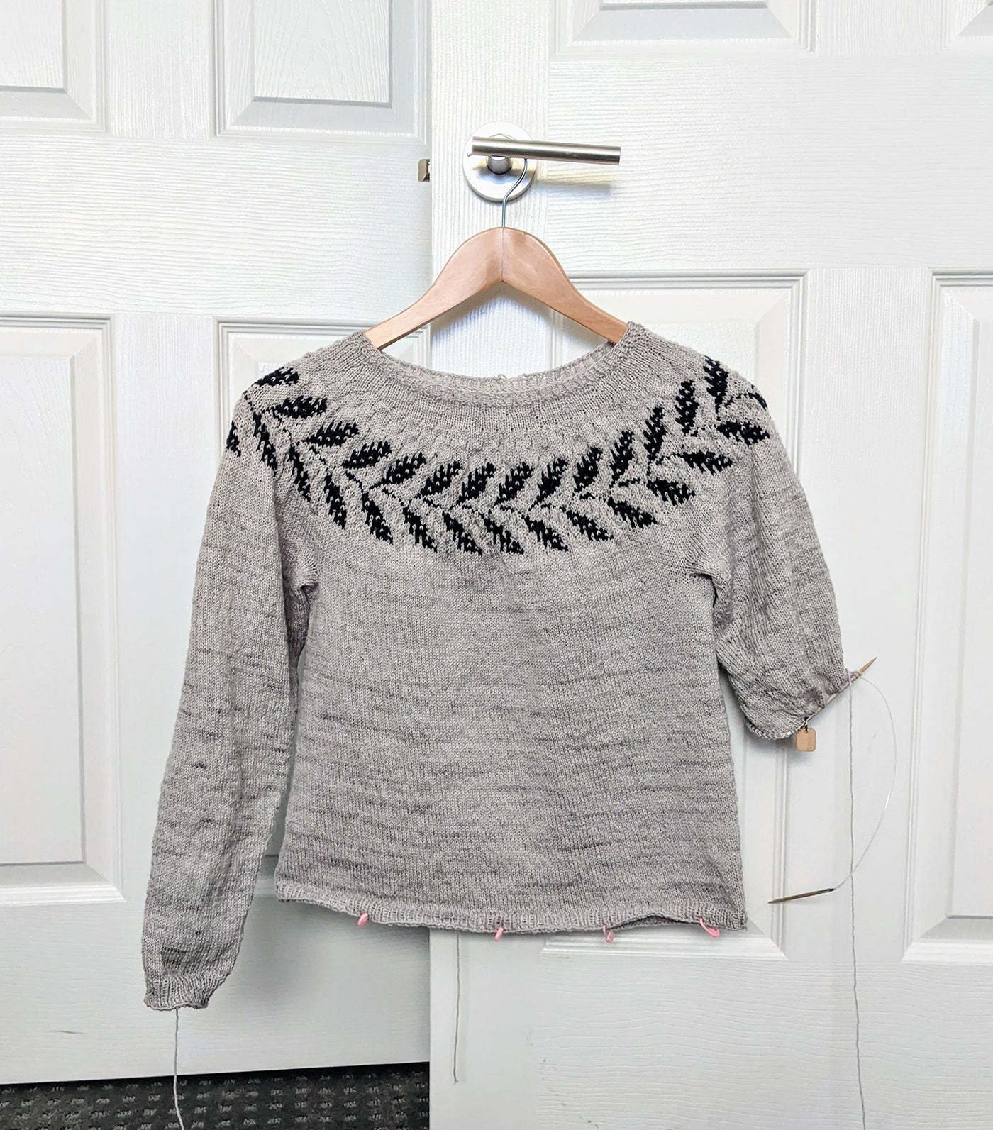 Image of a partially finished sweater hanging on a hook