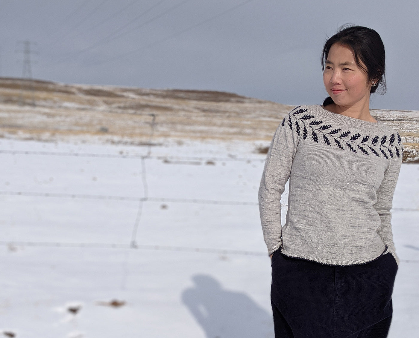 Woman standing in a snowy field wearing a hand knitted sweater featuring a decorative collar.