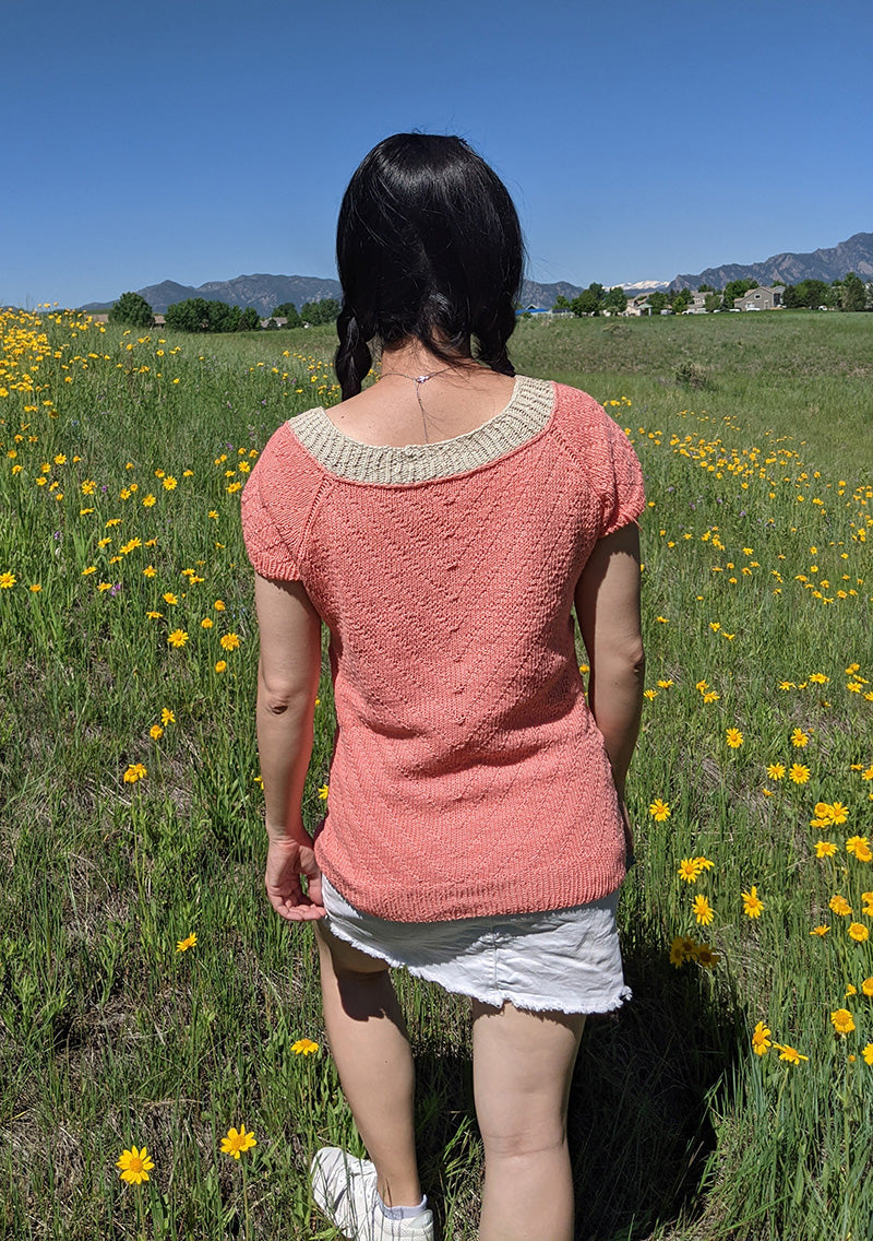This is a photo of a woman's back as she is walking away wearing a pink short sleeved sweater with a knitted patterned back and natural yarn colored neckband.