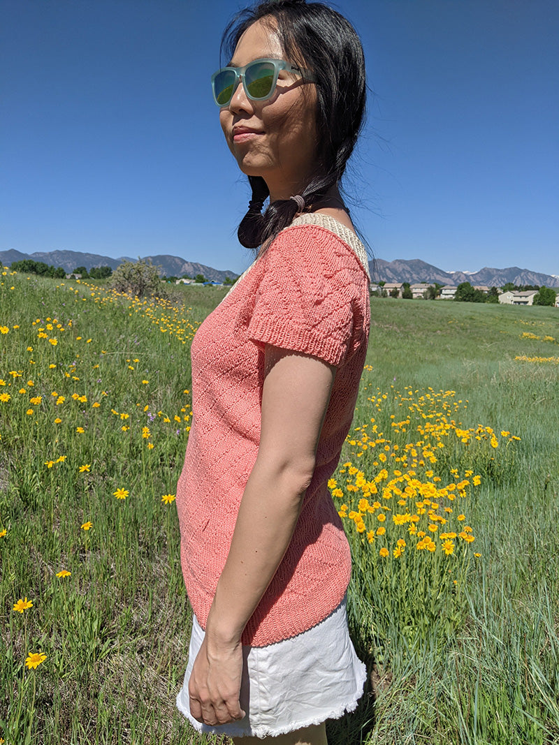 This is a photo of a woman from the side, showing off the sleeve of a knitted short sleeved shirt in pink. She is standing in a field of yellow flowers.