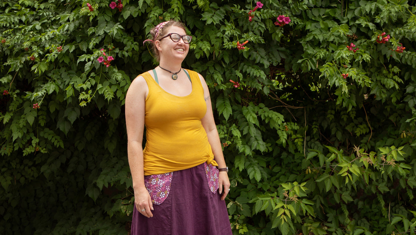 This is an image of a woman in a yellow tank top standing in front of shrubbery