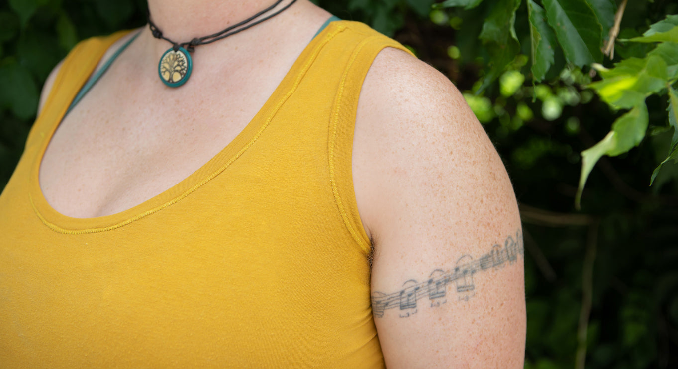 this is an image of a yellow tank top up close and looking at the stitching along the neck and arms