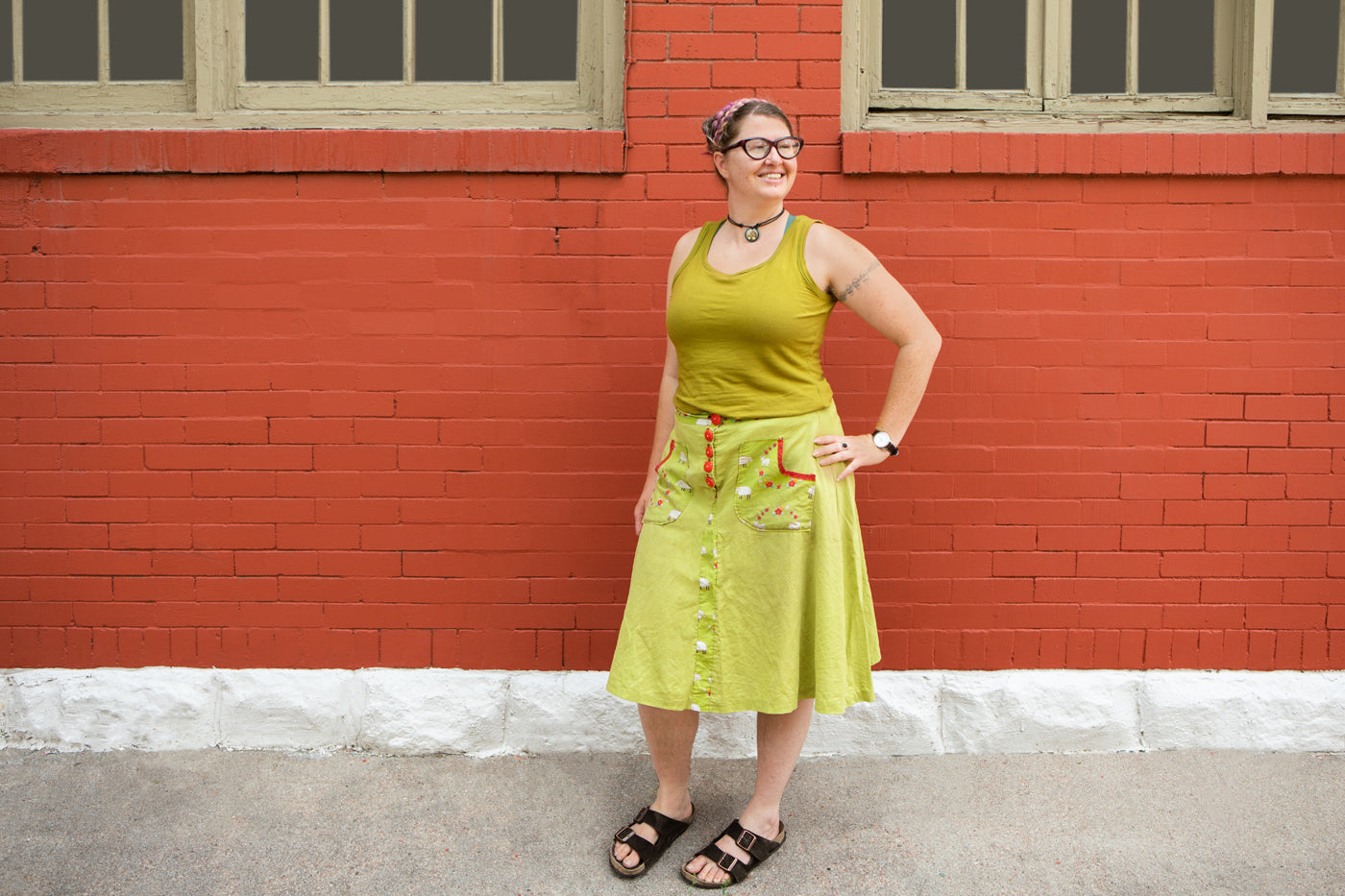 This is an image of a woman wearing a chartreuse tank top and green skirt standing in front of a red brick building