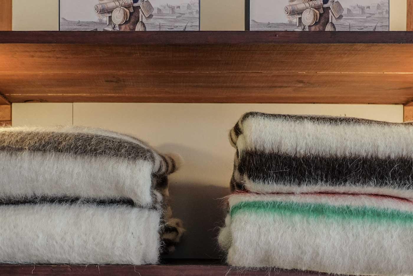A stack of Portuguese brushed wool blankets (Cobertor de Papa) on a shelf