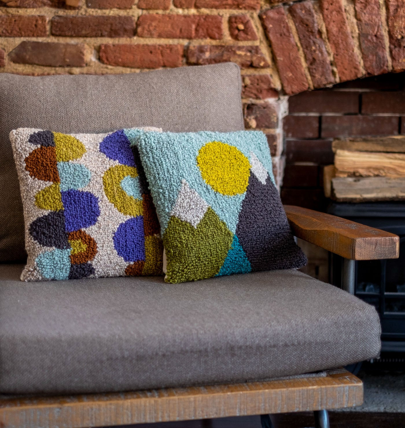 Two punch needle throw pillows on a chair near a brick fireplace