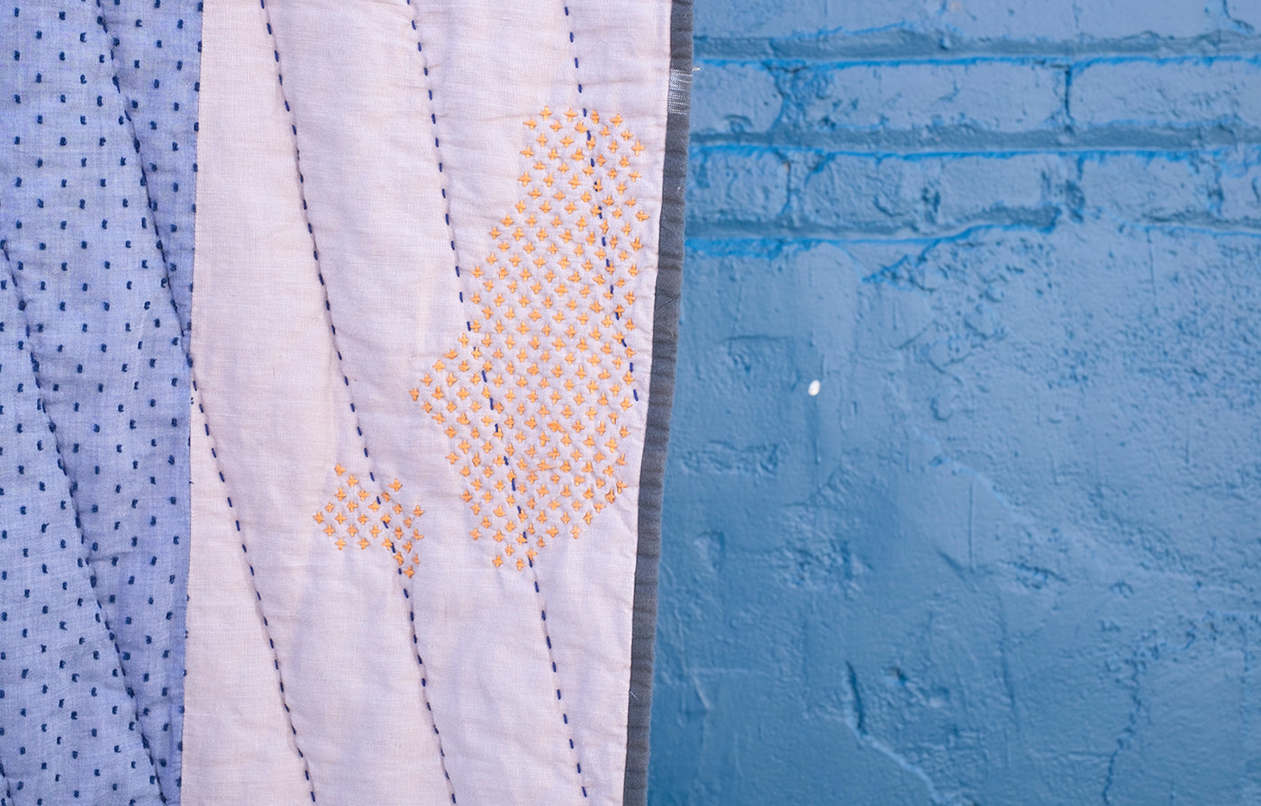 Photograph showing fuzzy dots on the chambray quilt, with random bits of sashiko embroidery accents to lend some tactile interest.  Photograph is up close showing the detail, with a blue background.  Quilt is blue and grey with orange accents of threading.