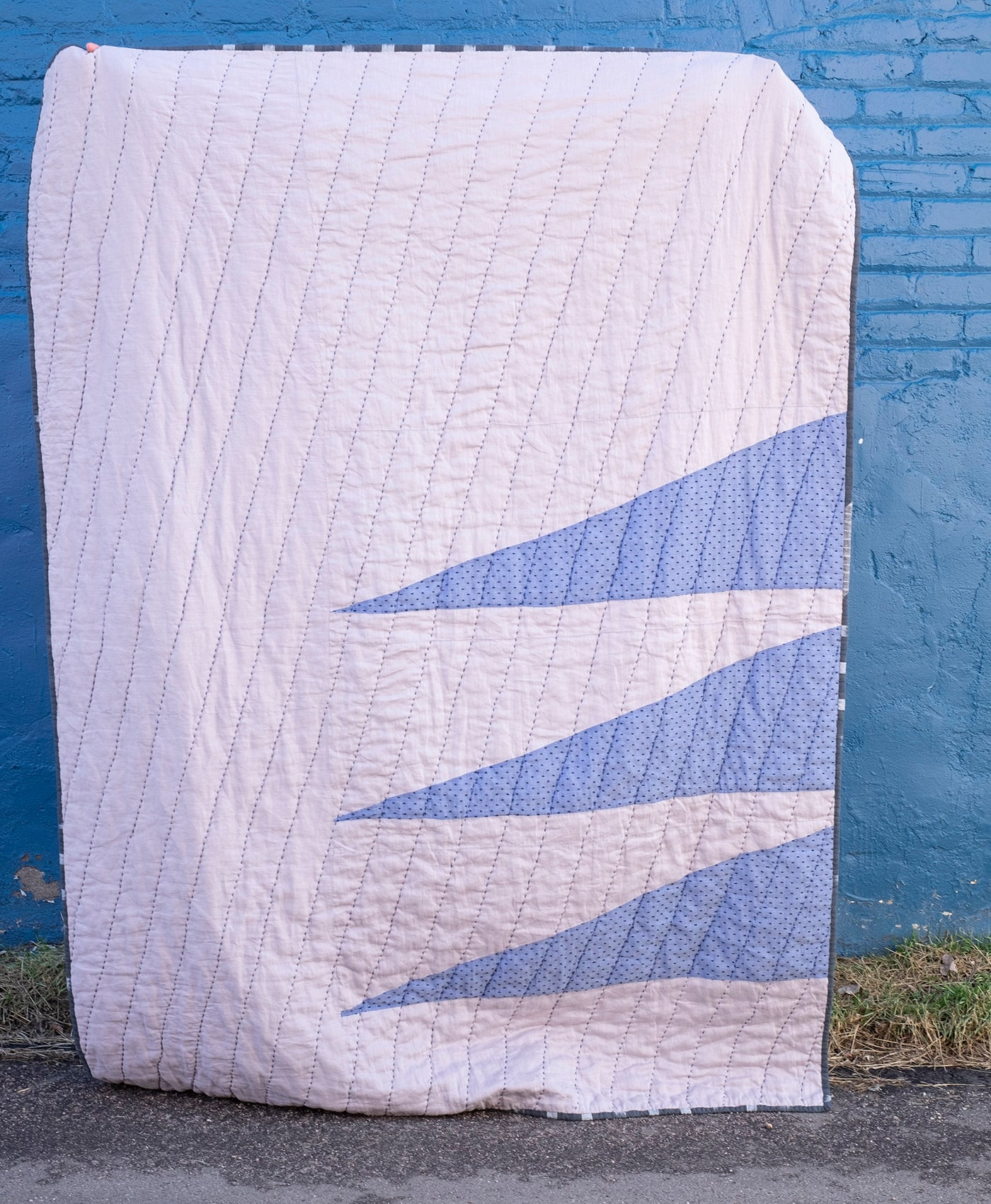 Quilt in darker sky blue with navy fuzzy dots on the chambray in triangles.  These blue triangles are on a gray fabric. Quilt is being held up vertically with the triangles on the right side.  Background is a dark blue brick wall.