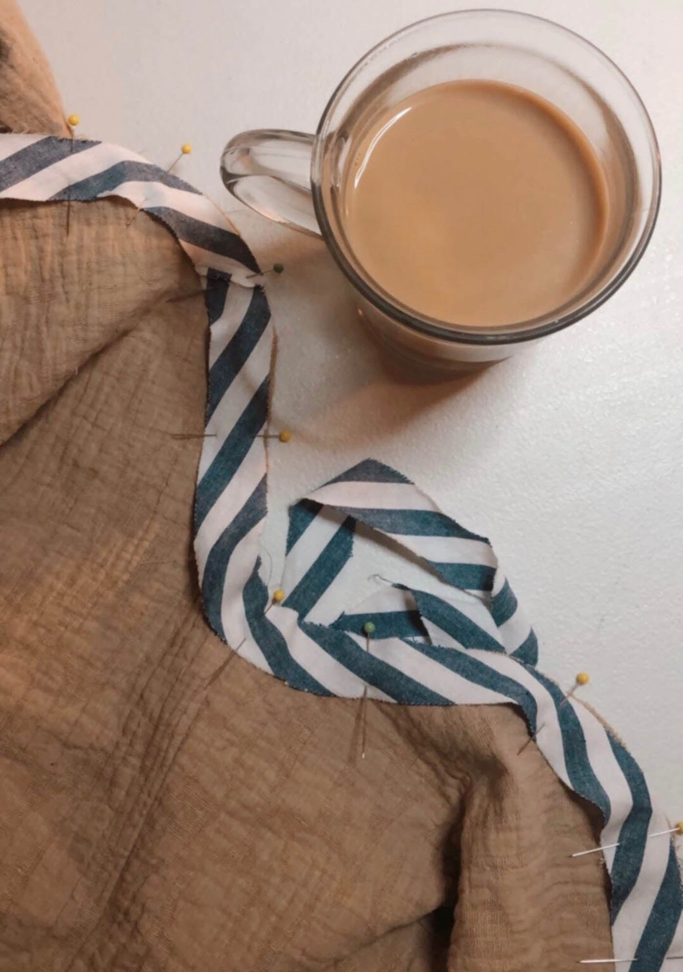 Lay flat image of sewing project and a cup of coffee