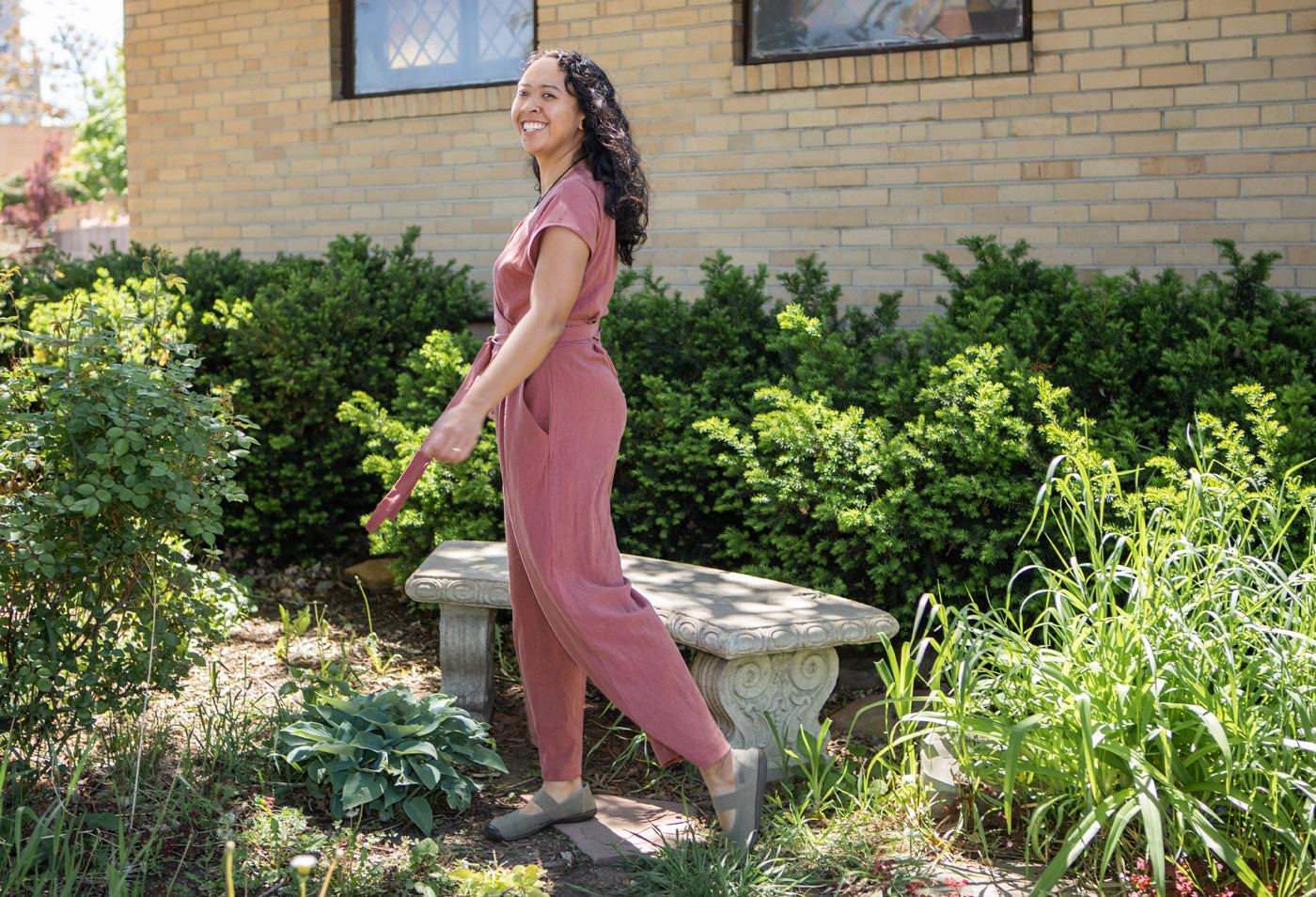 Woman posed in a garden area wearing a pink jumpsuit with a view from the side