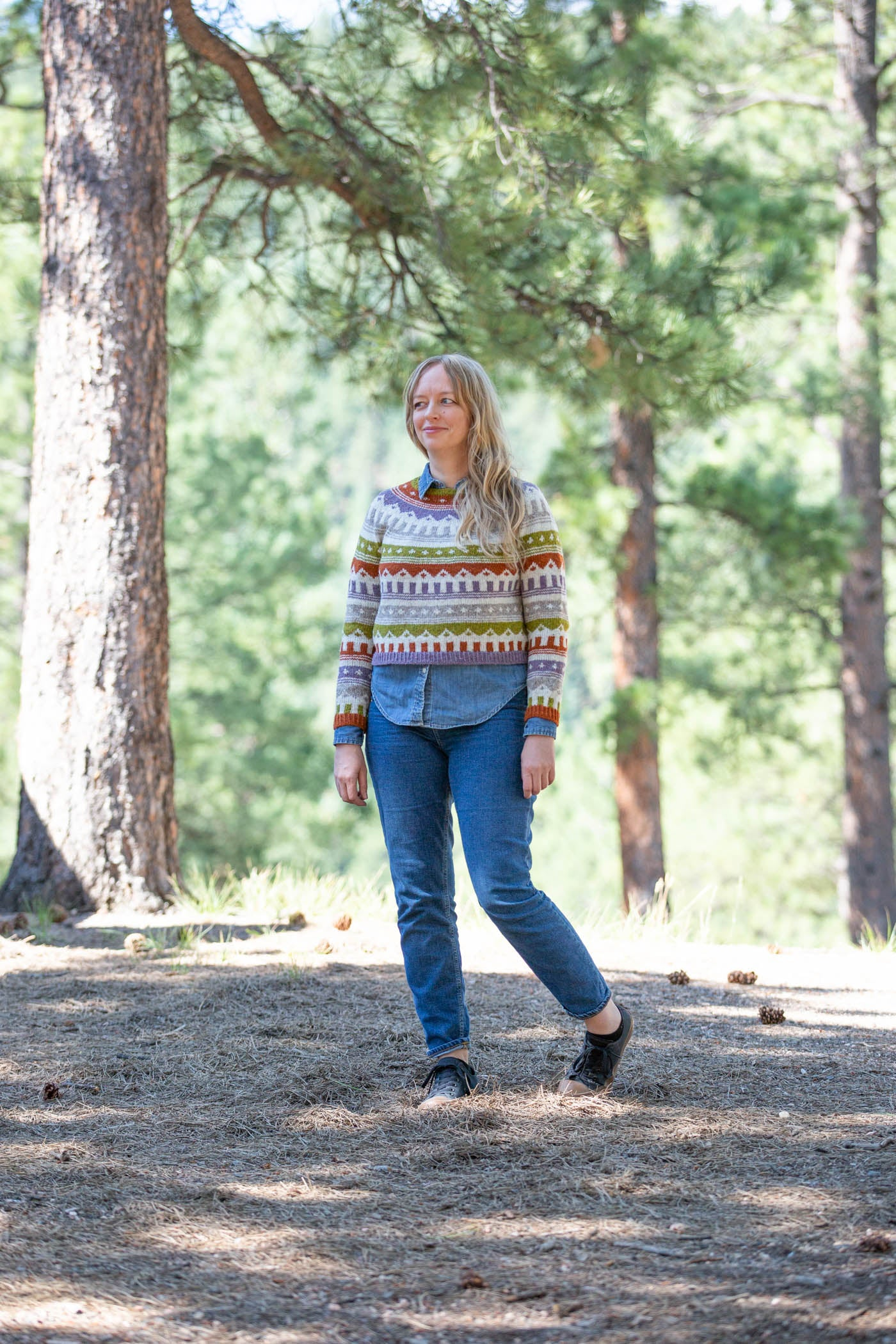 Women standing in evergreen tress facing the camera smiling.  Wearing a multi colored knitted sweater and jeans.
