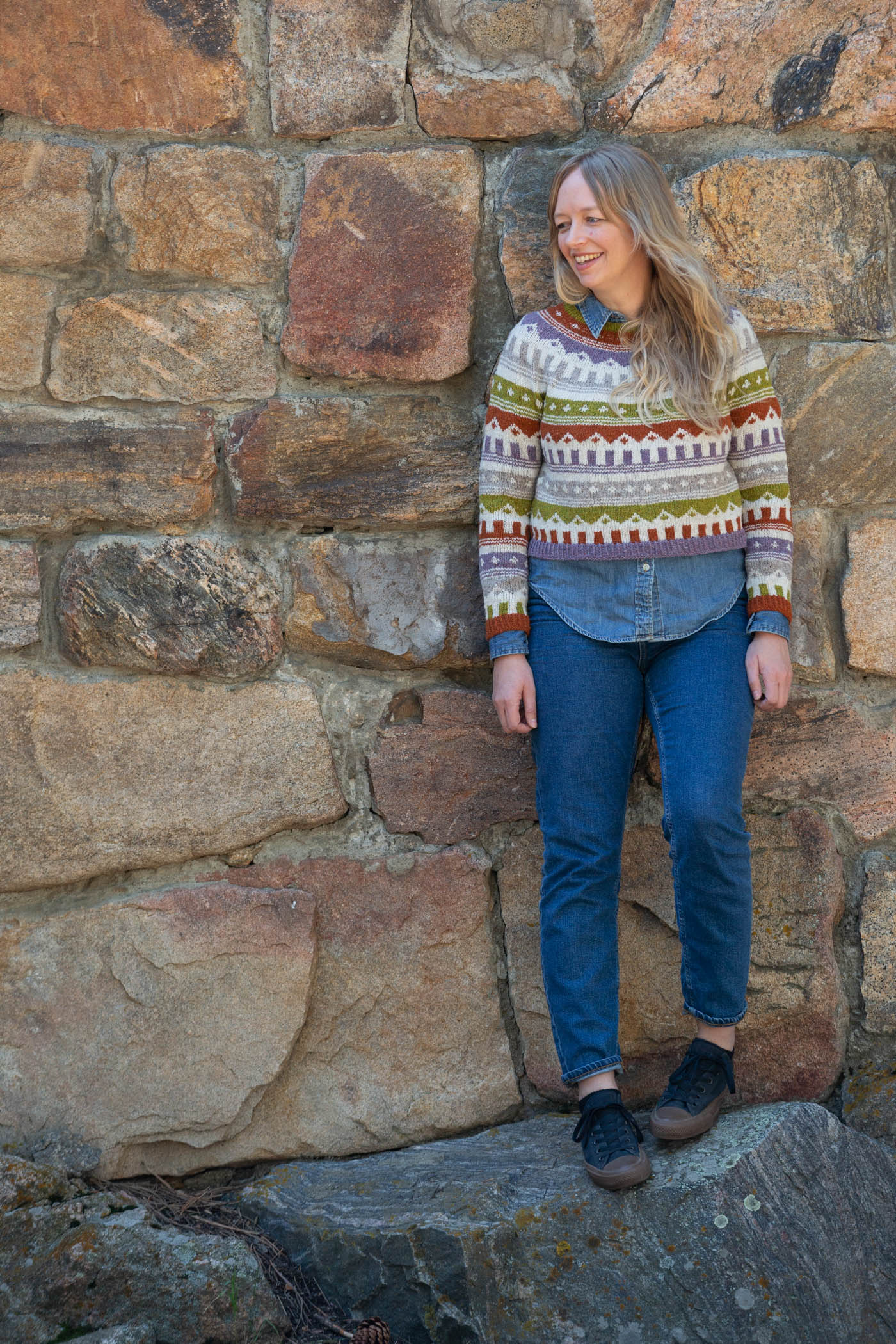 Women standing against a stone wall looking over her right shoulder smiling. Women is wearing a multi colored knitted sweater and jeans.