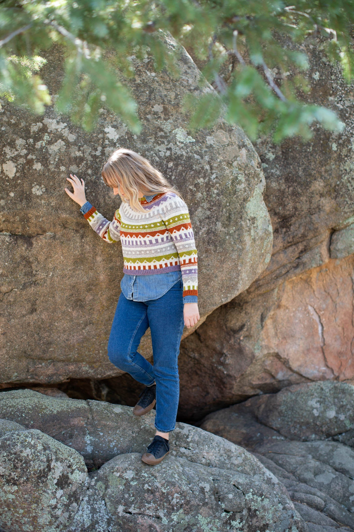 Women wearing a multi-colored knitted sweater and jeans looking down to the right.  Women is standing on large mountain rocks, using her right hand to brace agains the rock.