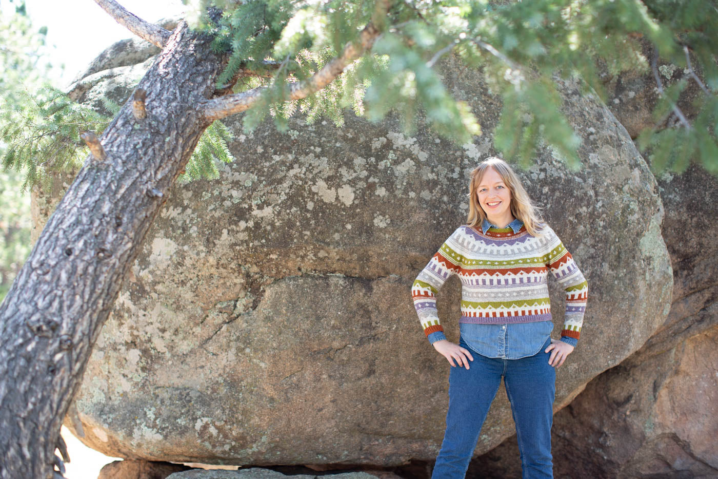 Women standing in front of a large mountain rock, facing the camera, wearing a mutli-colored knitted sweater and jeans.  Women has her hands on her hips looking at the camera smiling.  In the foreground is a tilted evergreen tree.