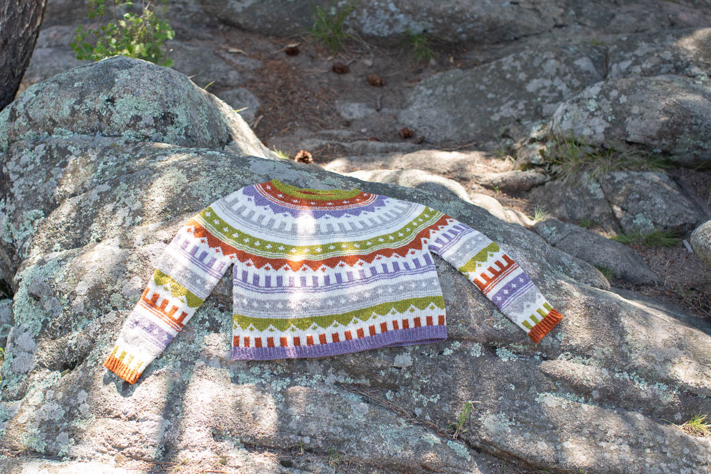 Multi colored knitted sweater, laying flat on a rock.