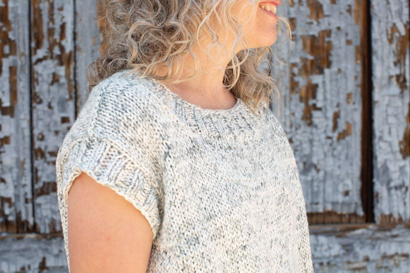 Detail photograph of a women wearing a knitted sweater, standing in front of a wooden wall with grey peeling paint.  The photograph highlights the ribbing on the knitting on the neckline and arm holes.