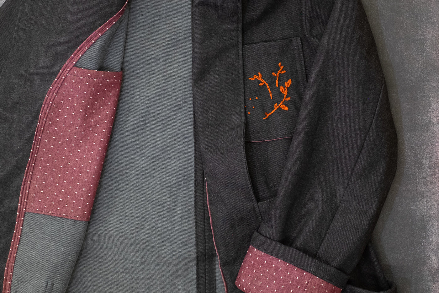 Demin Jacket laying flat showing the second fabric selection in a light maroon for the inside pocket, cuff and an orange detail on the outside pocket.