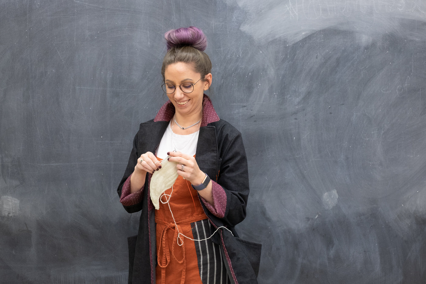 Women standing in front of a chalkboard, knitting wearing a Denim Black jacket, orange jumper with a white t-shirt.  The women's hair dyed in black/purple ombre is in a bun on the top of her head.