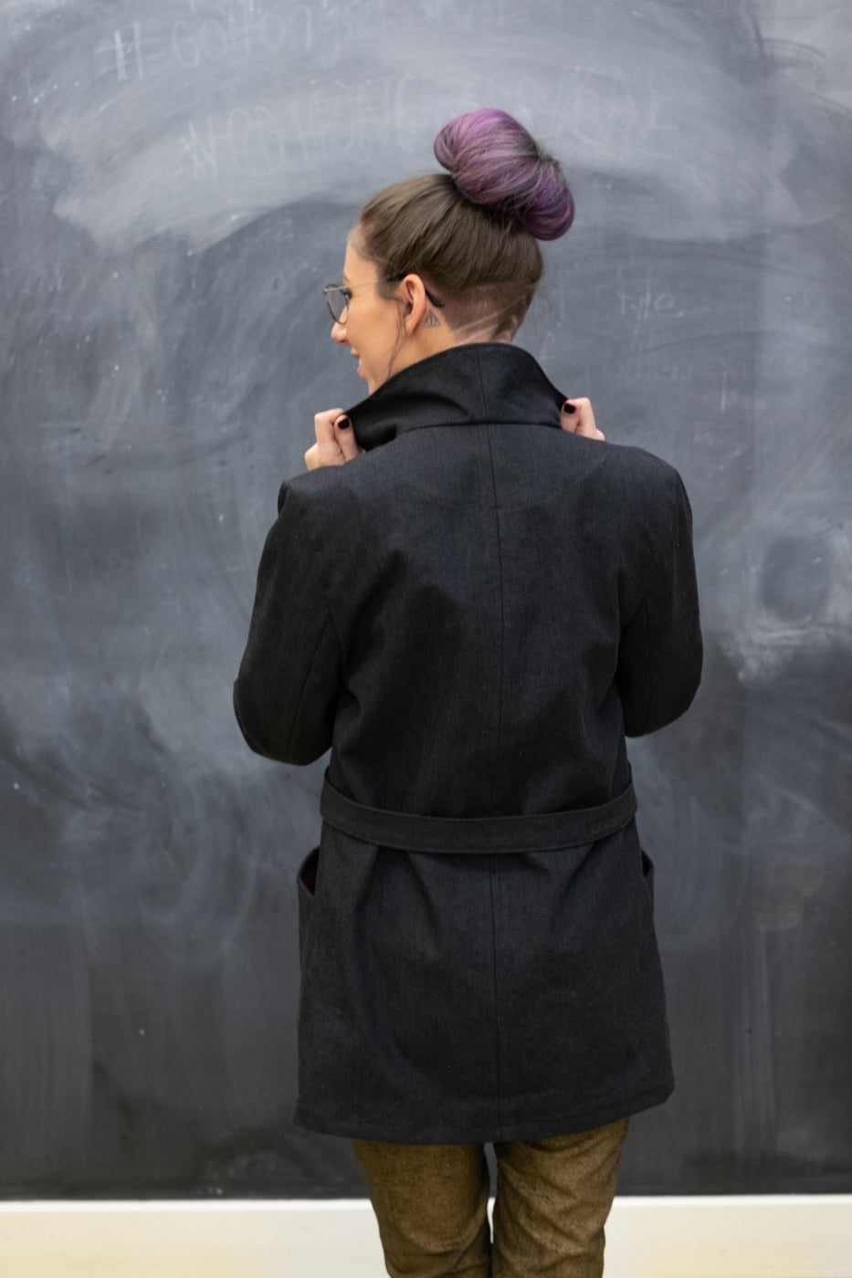 Women wearing Royo Denim Black jacket facing a chalkboard looking over her left shoulder with her handing holding the collar.