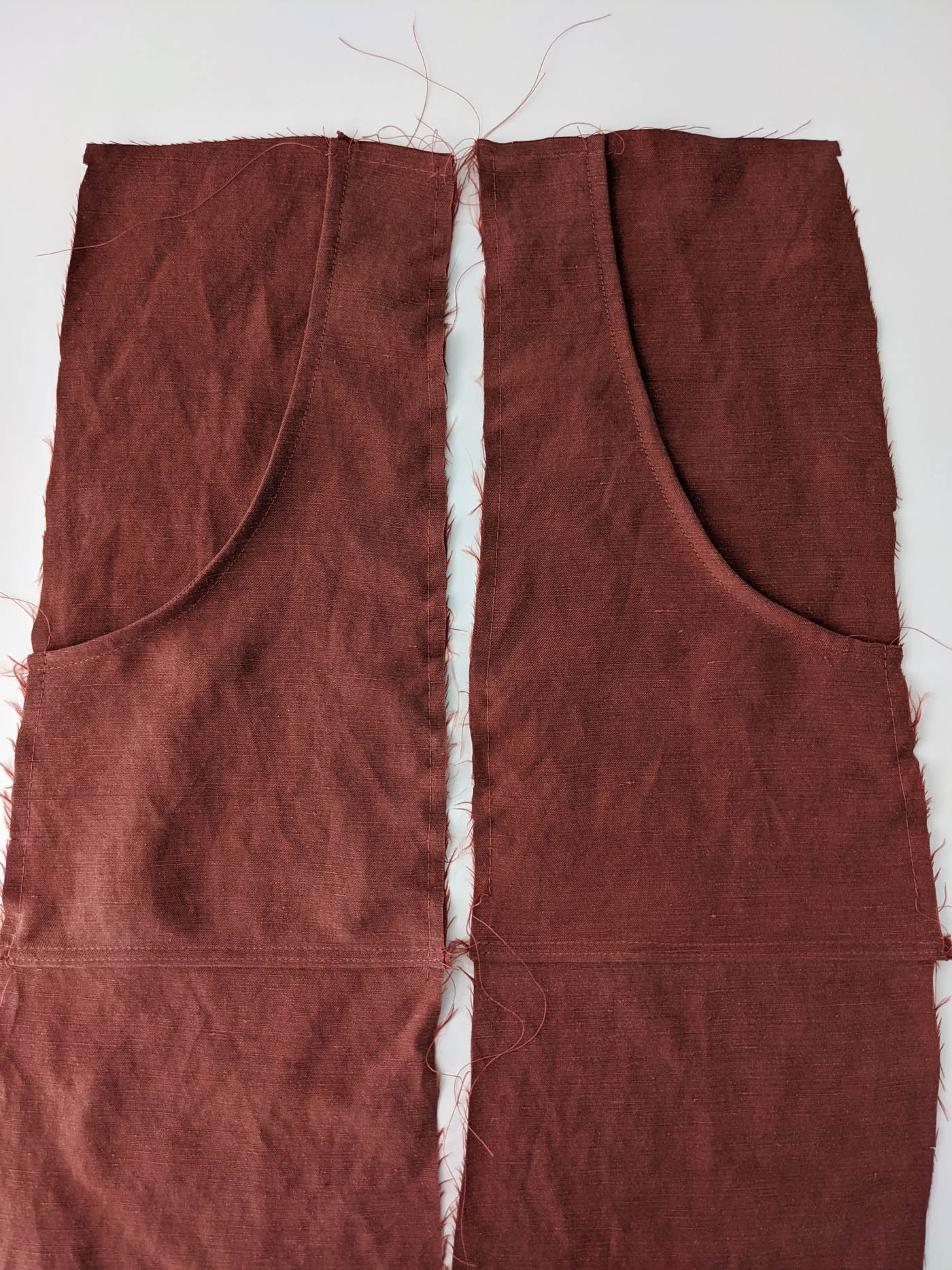 Photograph of lay flat with pattern laid out, looking straight down on fabric with pins holding the project in place. The cutouts are in a rust color against a white background.