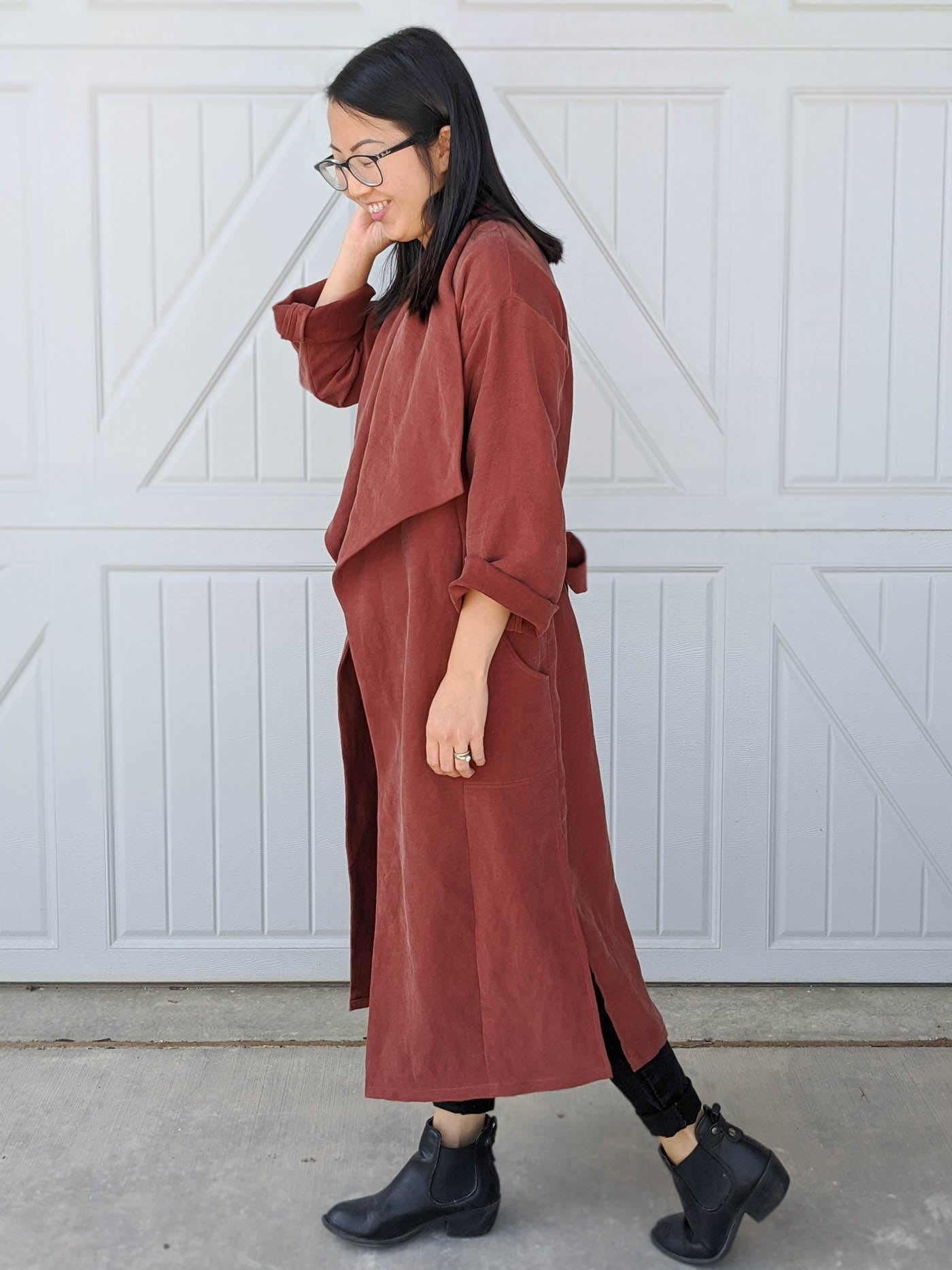 Women wearing the Cambria Duster in rust walking to the right with her left hand in her hair. Women is walking to the left in front of a white garage door.