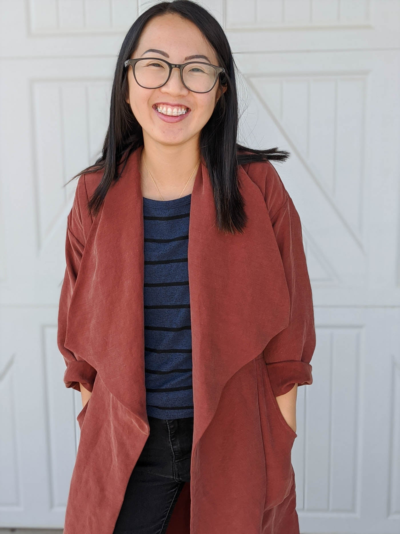 Up close photograph of a women wearing the Cambria Duster. Women is wearing glasses, facing the camera, hand in her pockets facing the camera and smiling. The background is a white garage door.