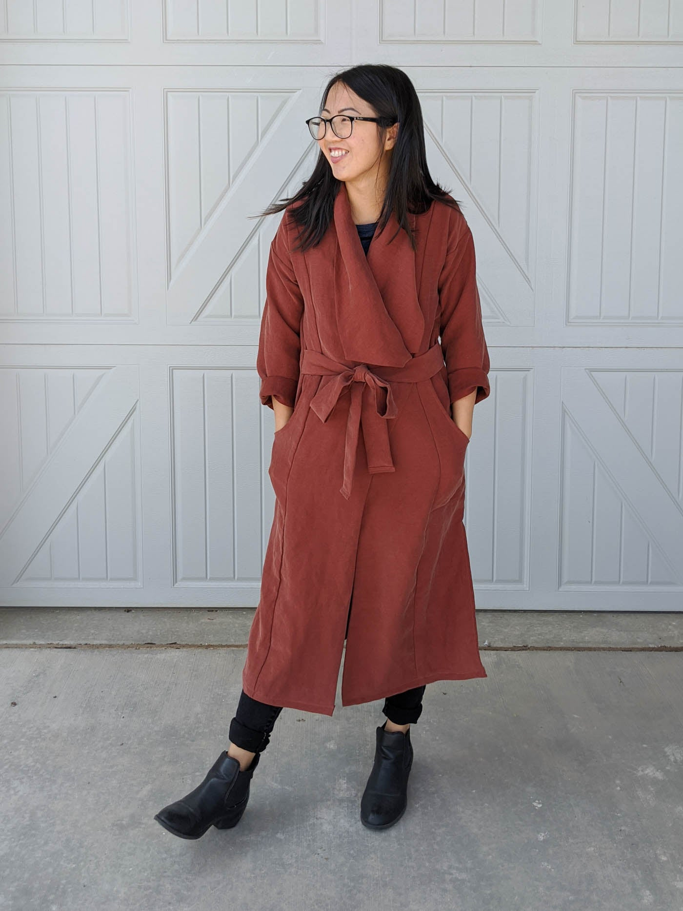Women wearing a Cambria Duster in rust with the duster tied. Women is standing straight on to the camera, with her hands in her pocket looking off over her right shoulder and smiling. Women is standing in front of a white garage wall.