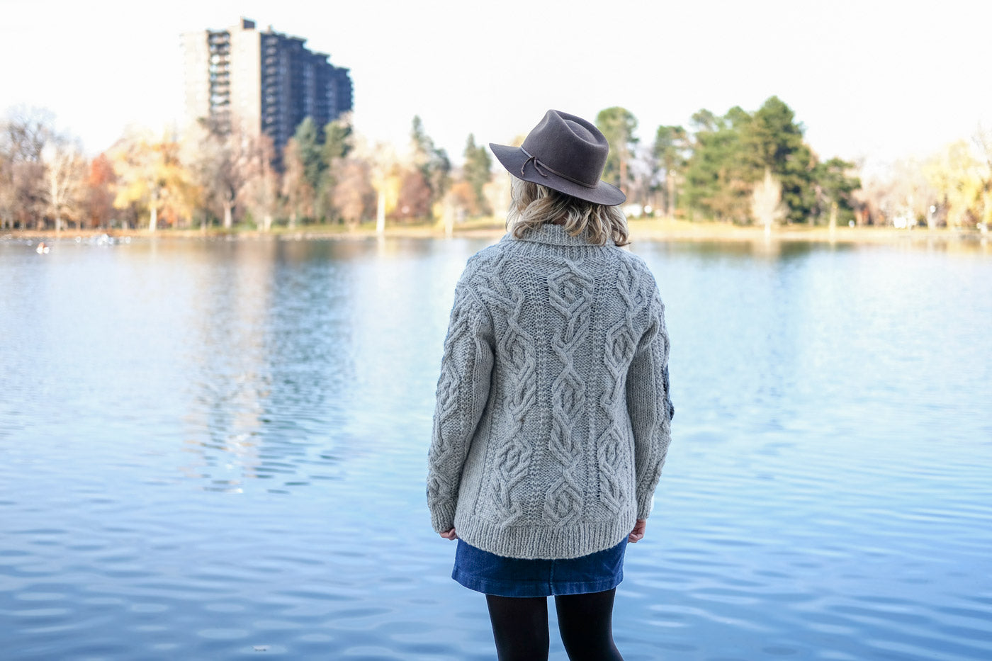 Amber looking out over a lake showing off the back side of her cabled cardigan