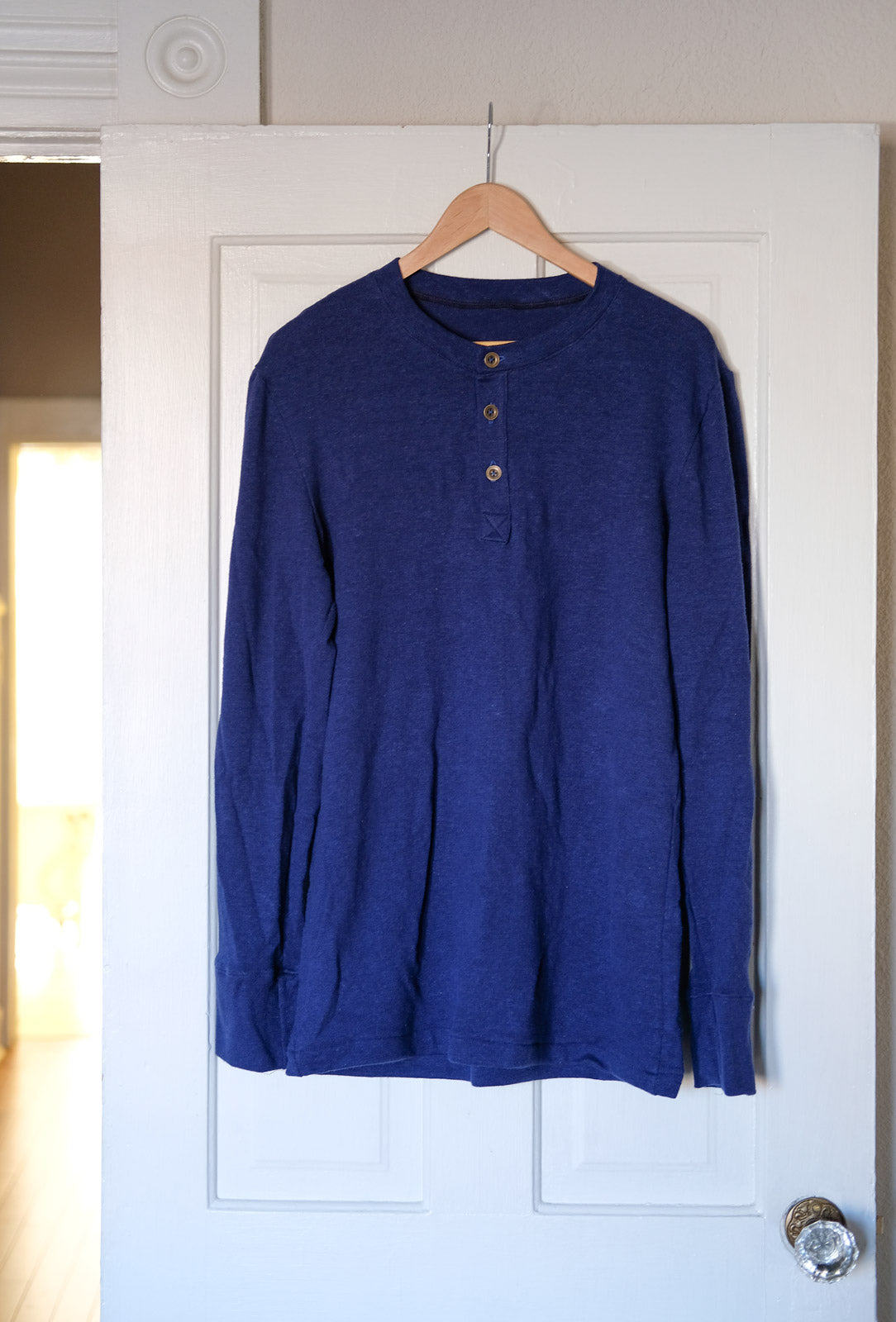 Royal Blue Thread Theory Henley hanging on a door