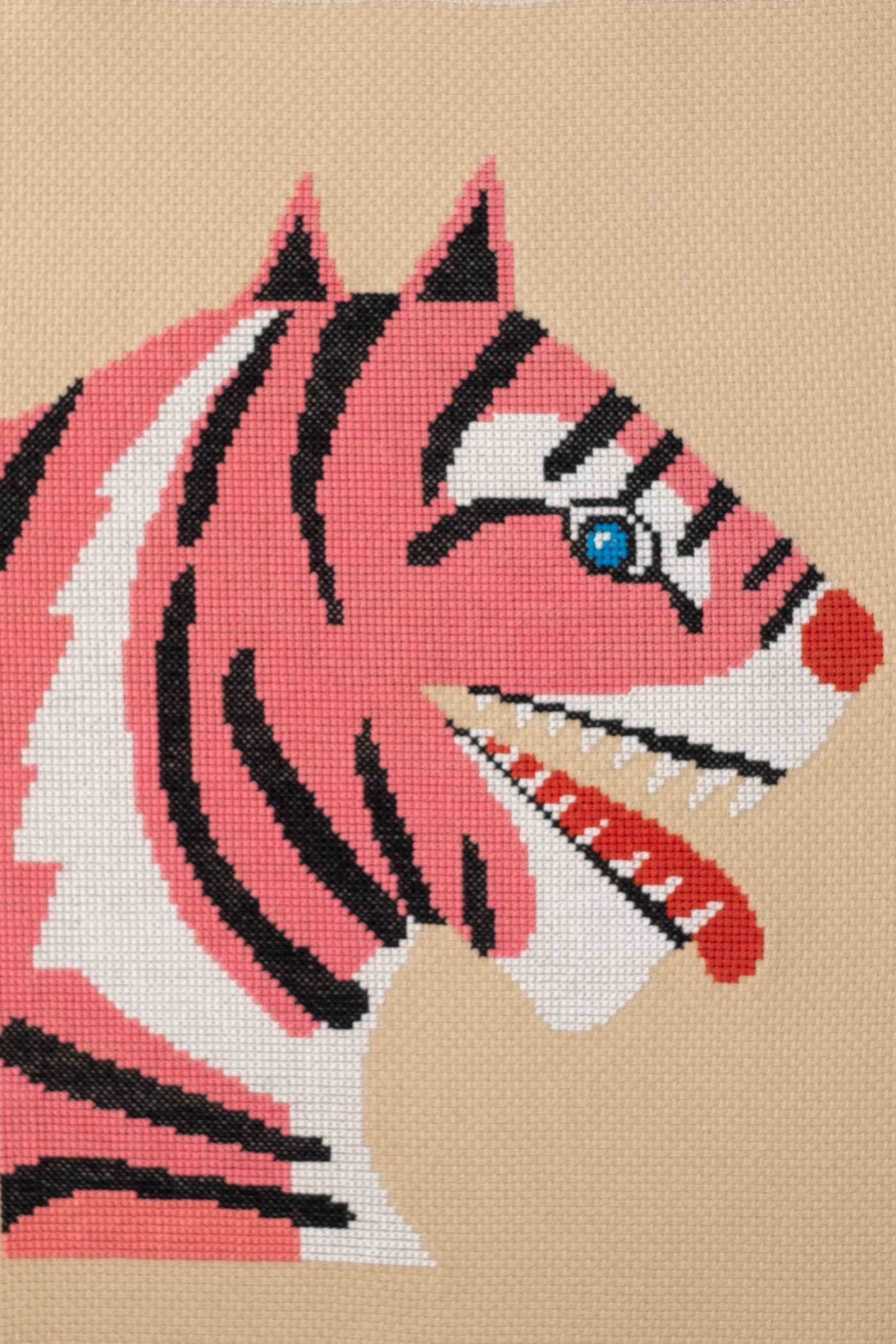 Lisa Congdon's Fangs Out Cross Stitch Kit of a tiger with blue eyes, red nose/tongue and striped in white, black and pink.