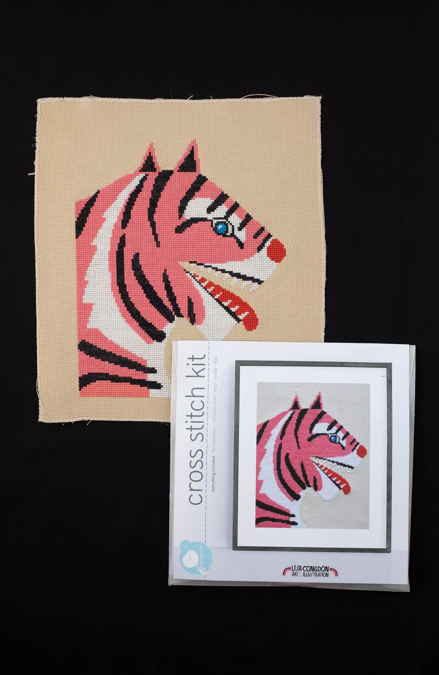 Lisa Congdon's Fangs Out Cross Stitch Kit of a tiger with blue eyes, red nose/tongue and striped in white, black and pink.  Lay flat photograph along with the packaging you buy it in.