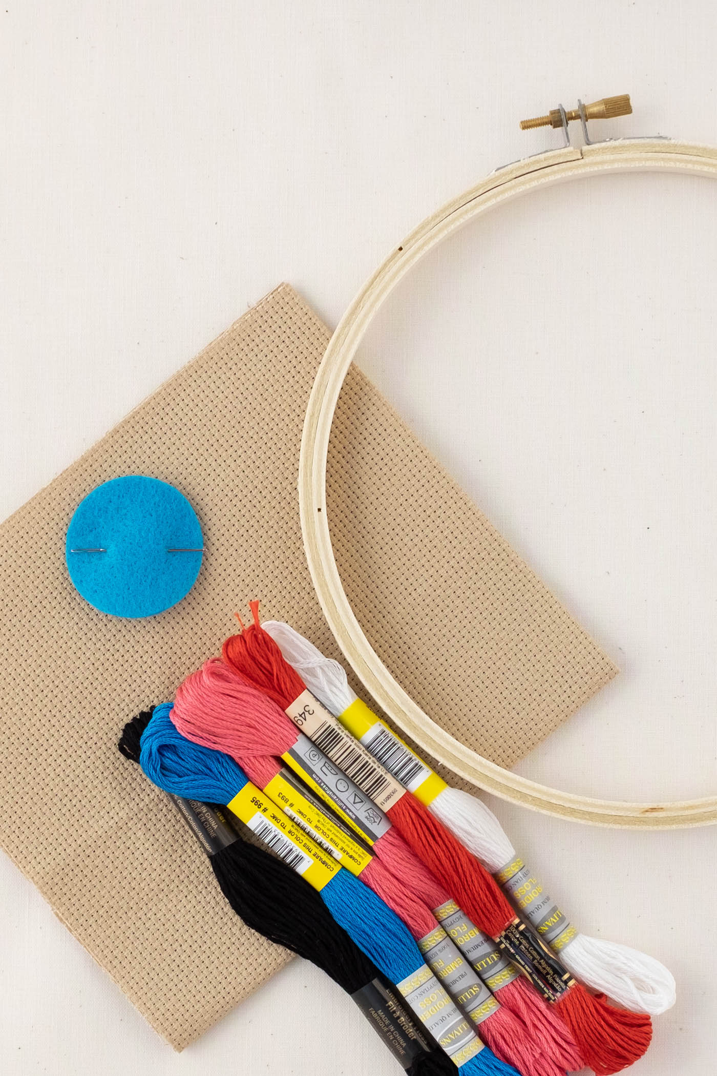 Lay flat of an embroidery kit with the backing, hoop, needle and black, blue, pink, red and white embroidery floss.