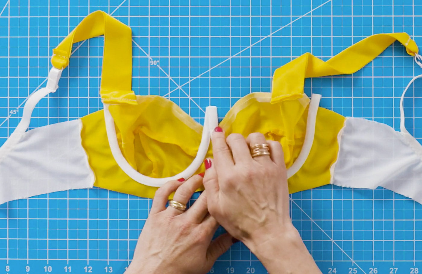 Hands placing the underwire casing onto an unfinished, handmade bra. The bra is color-blocked vibrant yellow and white and is laying on a bright aqua cutting mat.