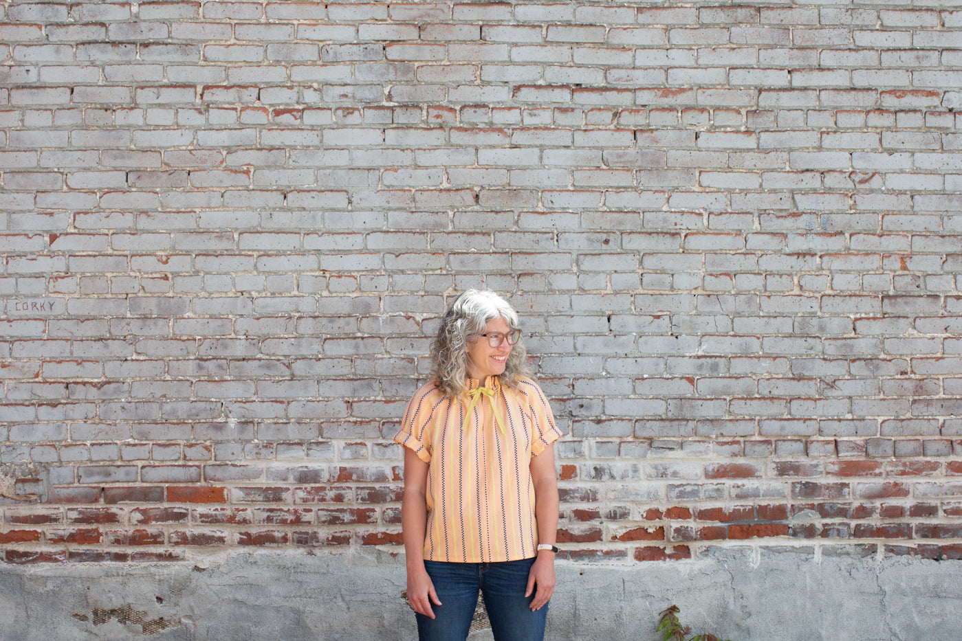 Jaime standing in front of a white washed  brick wall, looking off over her left shoulder smiling.  Jaime is wearing a peach vertical striped shirt with blue jeans.