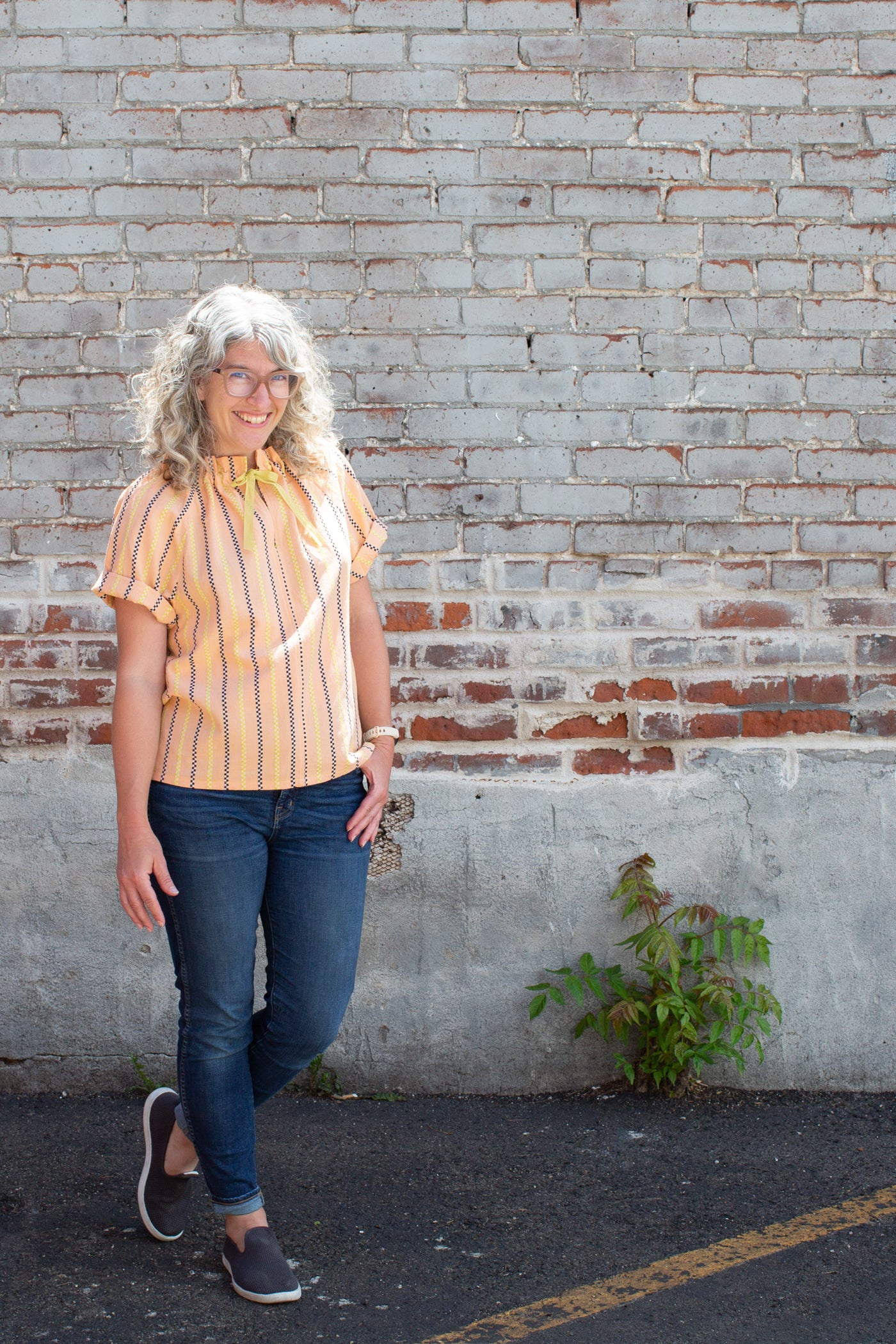 Jaime standing in front of a white washed  brick wall, turned slightly to an angle, facing the camera smiling.  Jaime is wearing a peach vertical striped shirt with blue jeans.