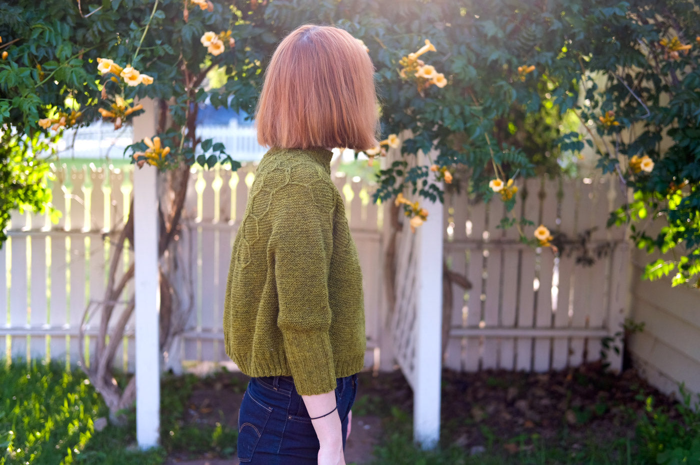 Lauren in her garden wearing her Wool and Honey Sweater