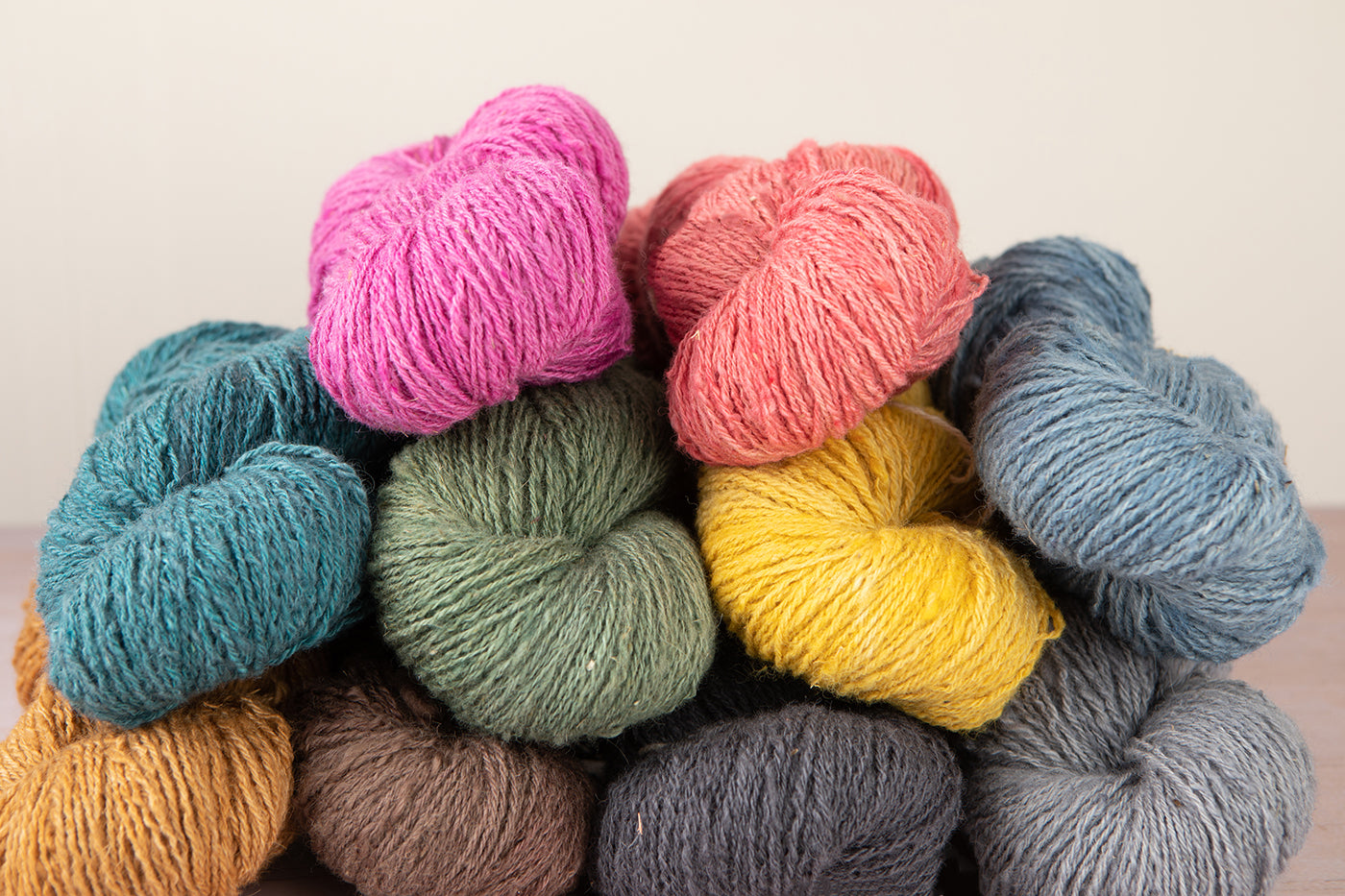 This is an image of several colorful skeins of yarn stacked up on a table.