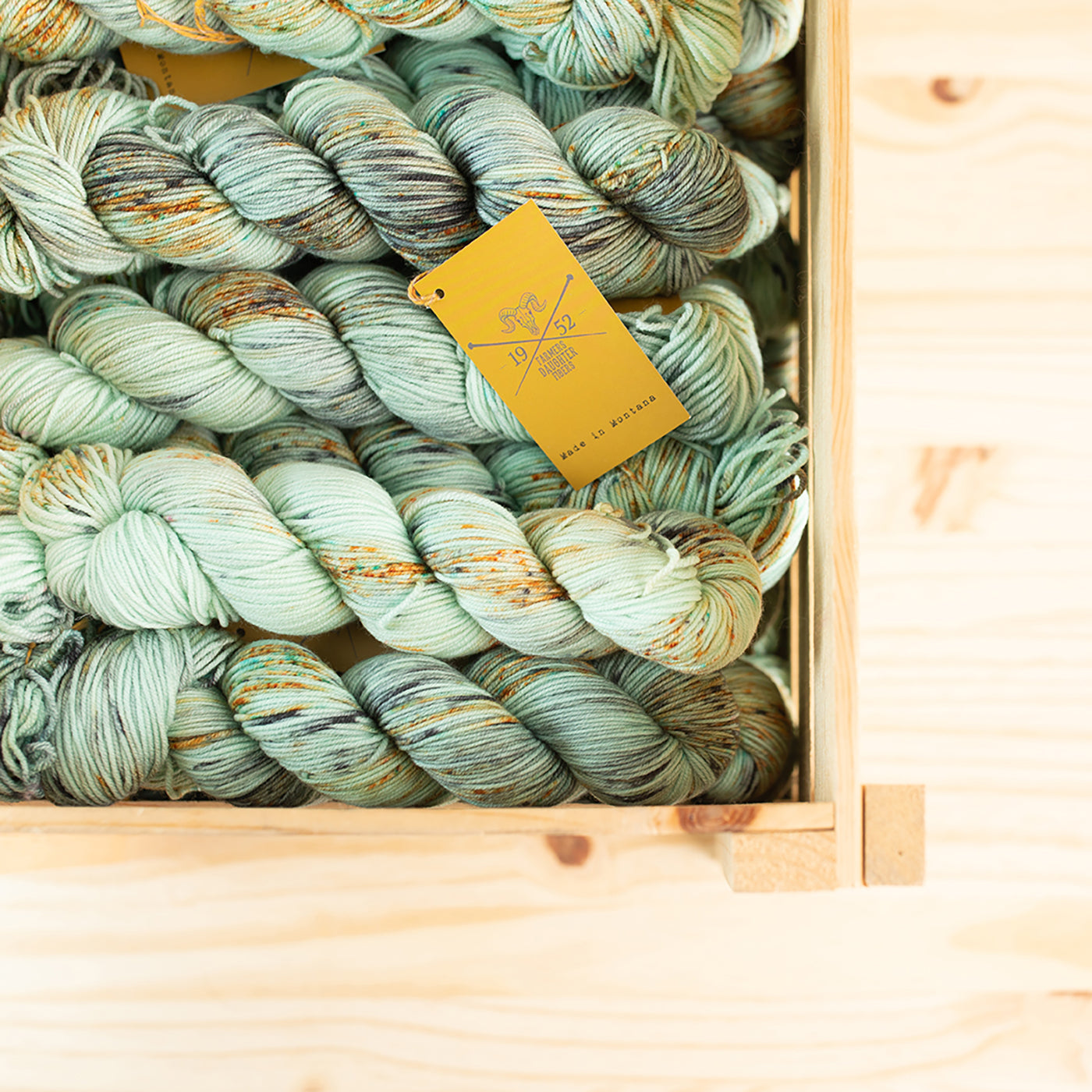 This is an image of a wooden box full of mint colored yarn.