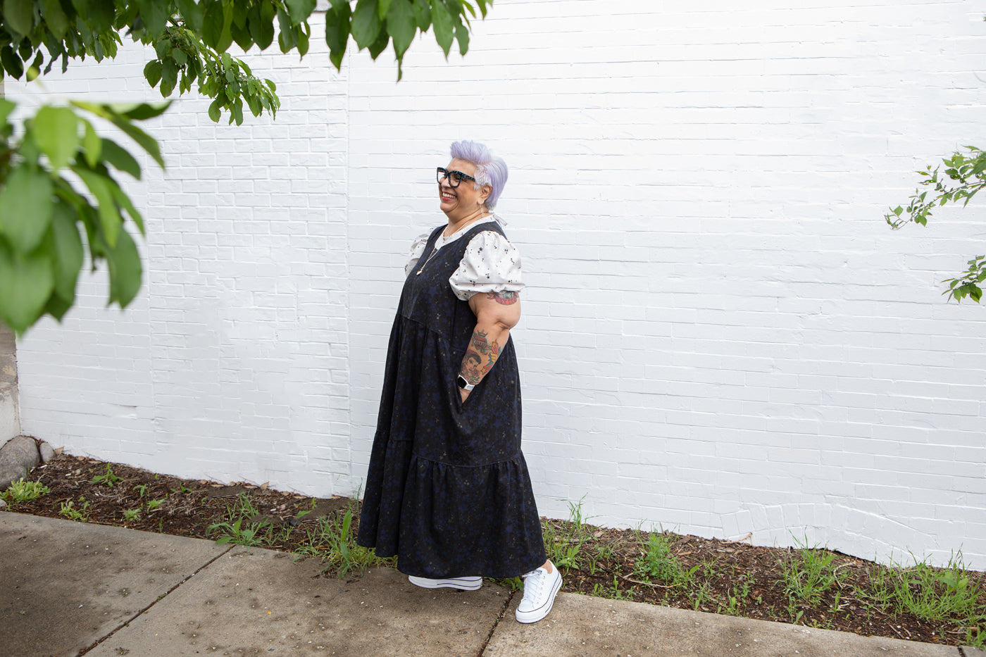 This is an image of a woman standing in front of a white brick wall wearing a black dress and white shirt