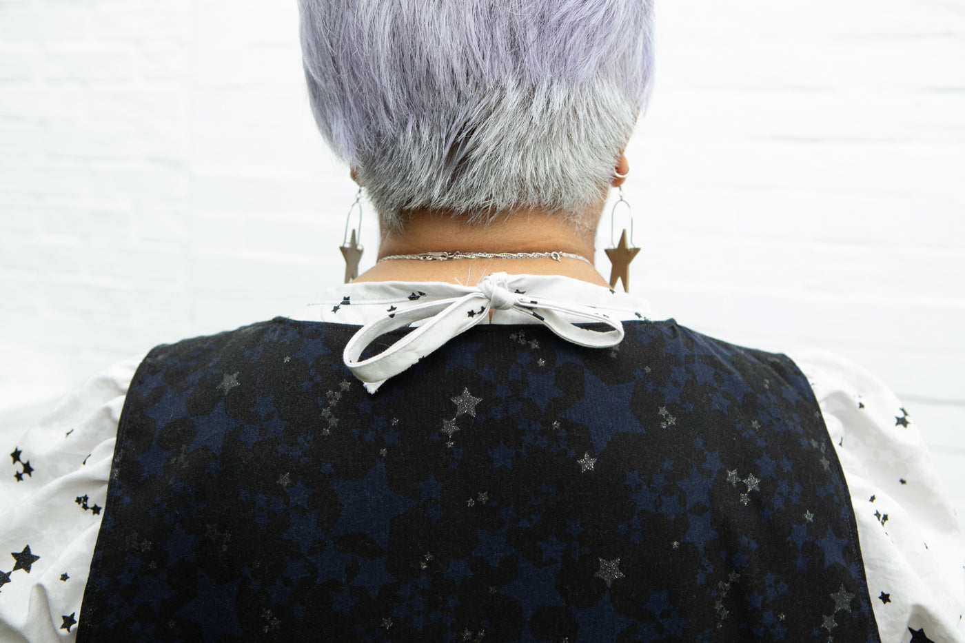 This is an image of the back of a woman wearing a shirt that ties closed at the neck. The fabric of the shirt she is wearing is white with stars on it and the dress she is wearing is black with stars on it.