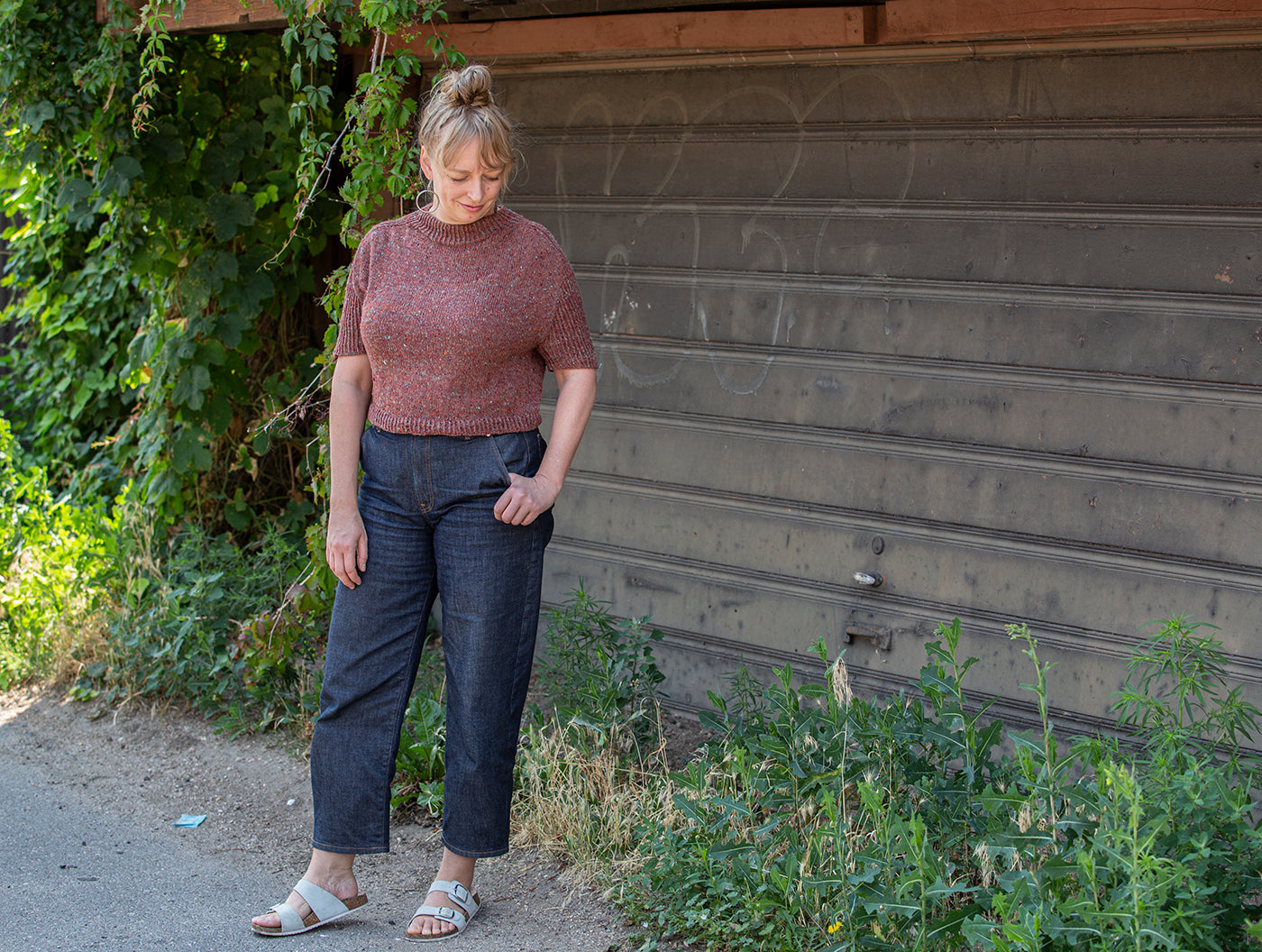 This is an image of a woman in a maroon sweater short sleeved shirt standing by some vines