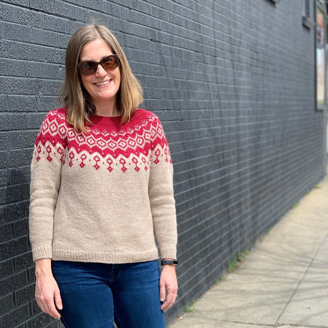 Lady in front of a dark wall wearing her knitted sweater that is tan and red with jeans.  Lady had sunglasses and is looking at the camera smiling.
