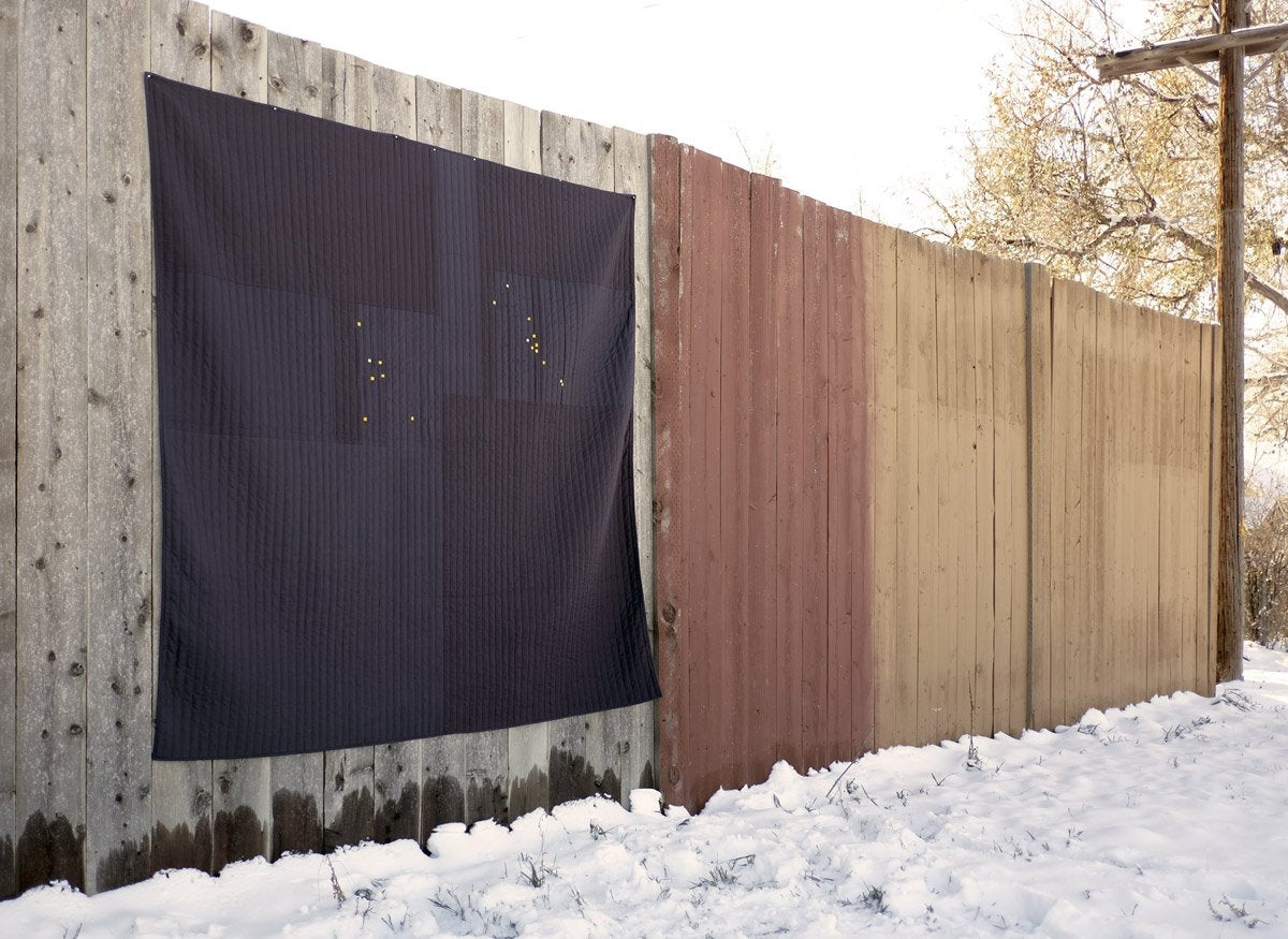 Constellation Quilt Hanging on a wooden fence
