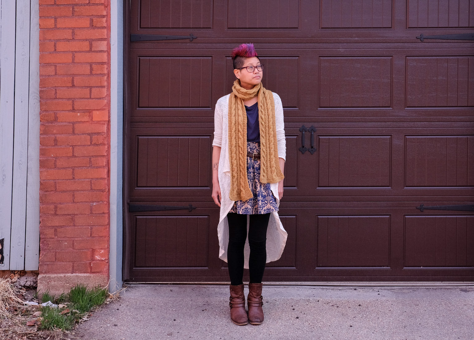 Woman with pink mohawk wearing mustard-yellow cabled scarf, standing in front of a dark brown garage door.
