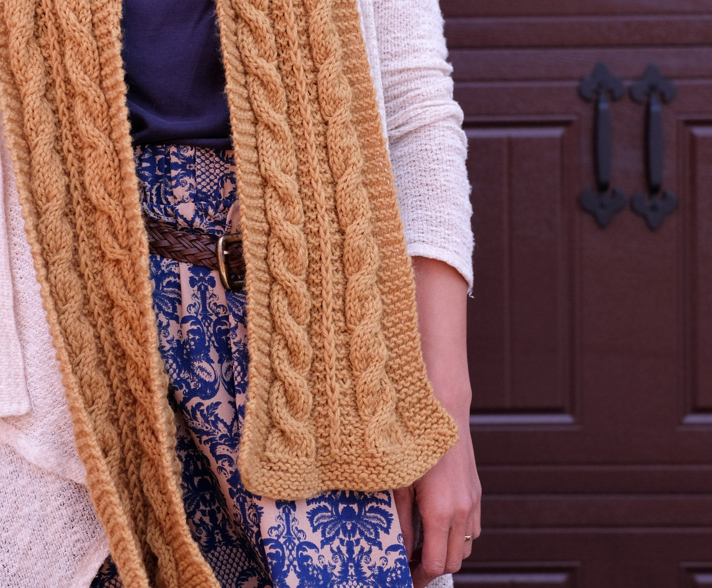 Detail of a handknit, mustard-yellow cabled scarf.