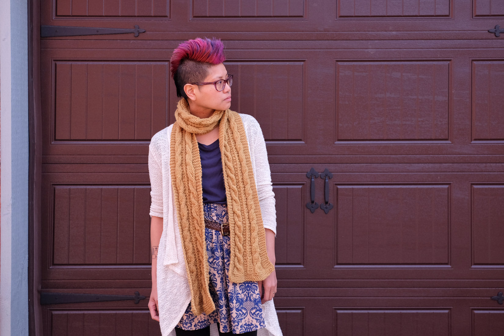 Woman with pink mohawk wearing mustard-yellow cabled scarf.