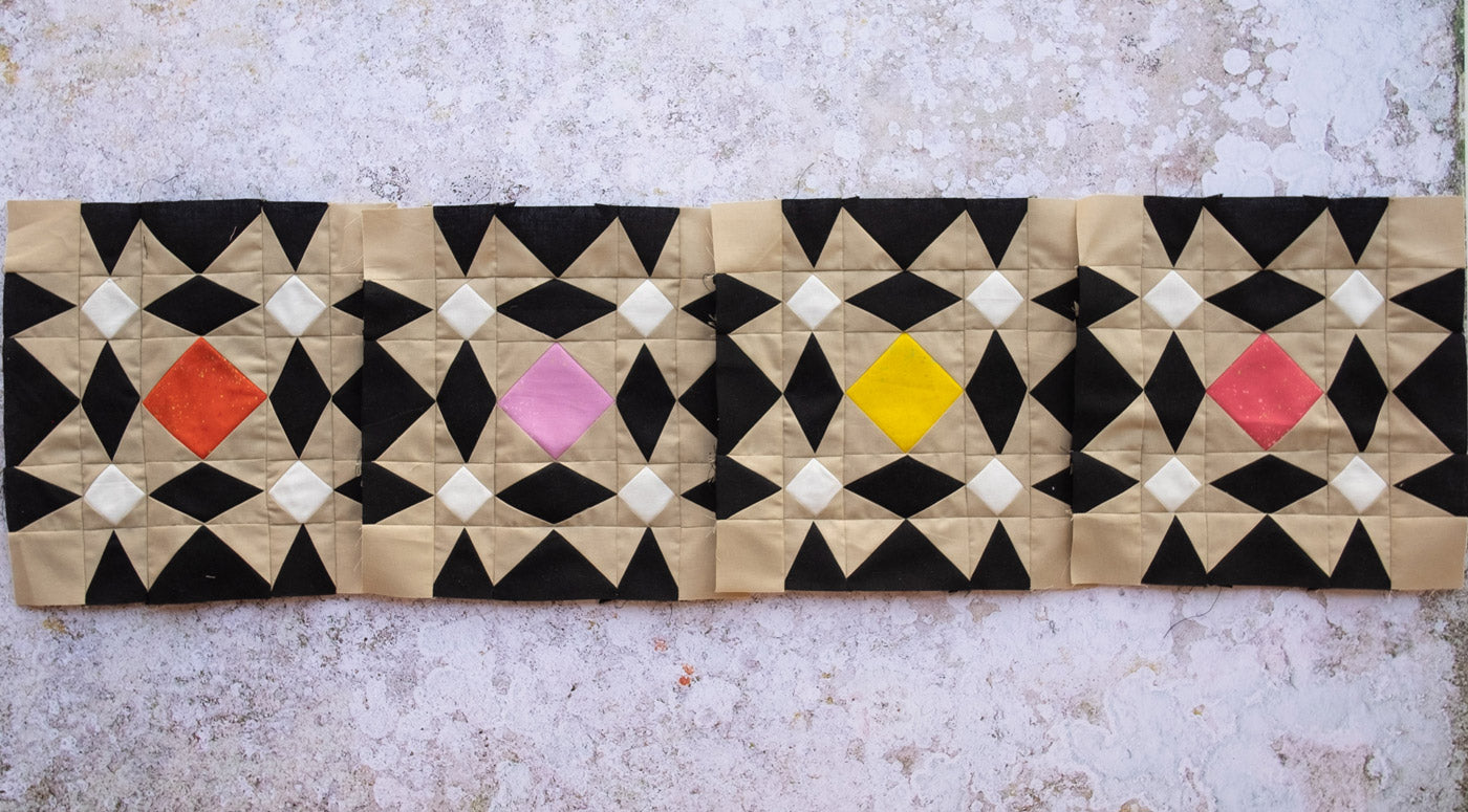 """Four quilt blocks laid out in a line making a """"row"""". The blocks are a high contrast geometric pattern that is reminiscent of patterned tiles."""