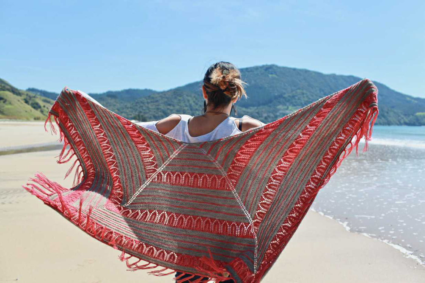 Outdoor photograph of a girl holding a brown/pink knitted shawl open.  Background is blue sky, mountain, ocean and beach.
