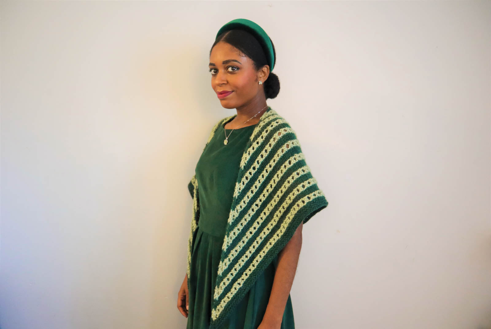 Women wearing knitted light green and spruce shawl over her shoulders. Women is wearing a spruce green dress, turned sideways with her left shoulder forward, looking at the camera smiling.