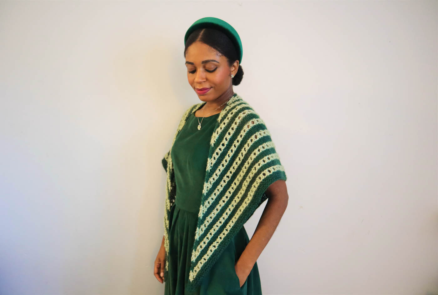Women wearing knitted light green and spruce shawl over her shoulders. Women is wearing a spruce green dress, turned sideways with her left shoulder forward, looking down with her left hand in her pocket.